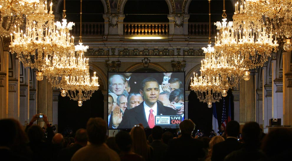People watch a big television screen broadcasting Barack Obama being sworn in as the 44th President of the United States of America on the West Front of the Capitol in Washington, Tuesday, Jan. 20, 2009 during a ceremony at the Paris town hall in Paris, France.