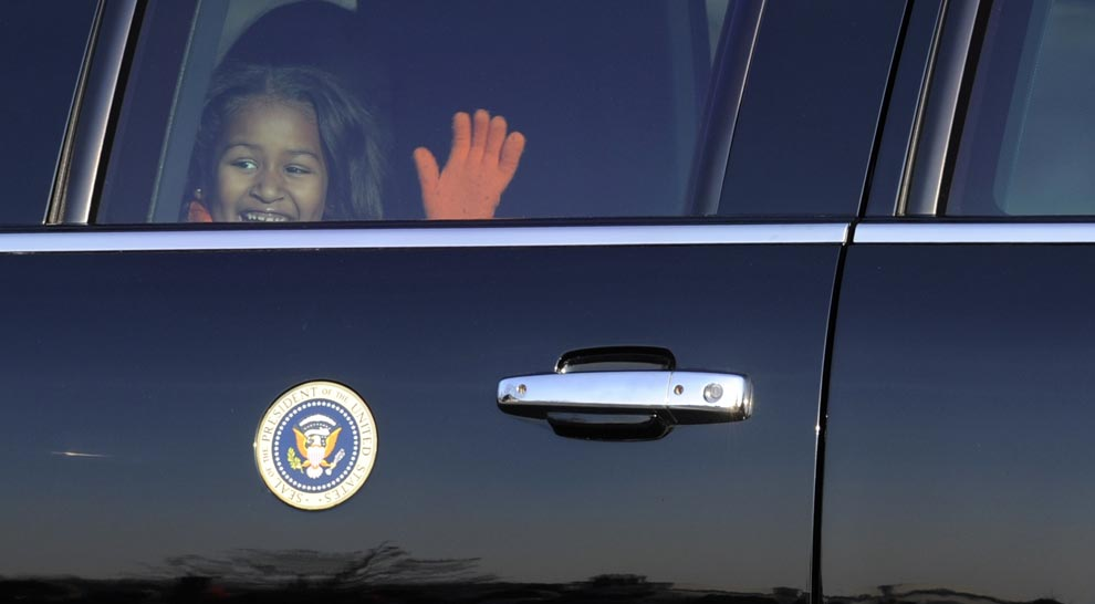 Sasha Obama waves through the limousine window as she and her sister Malia leave Capitol Hill in Washington, Tuesday, Jan. 20, 2009.