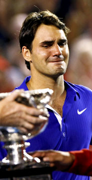 Roger federer looks emotionally at the trophy that he so wanted.